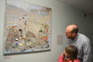 Adult and child looking at art hanging on the wall